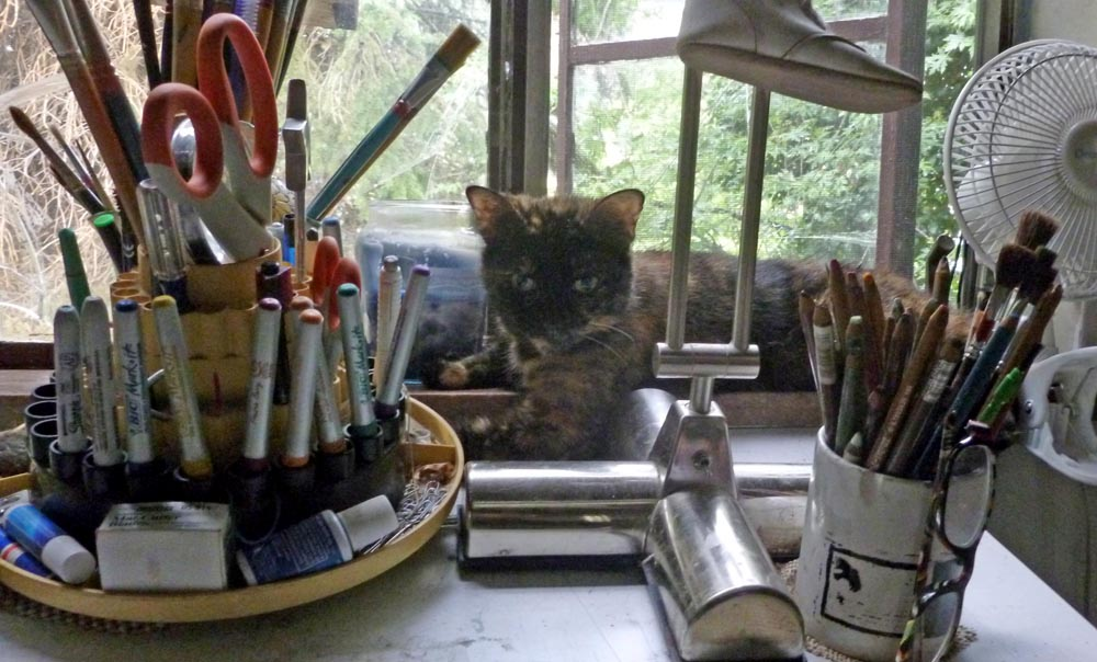 tortoiseshell cat looking at desk