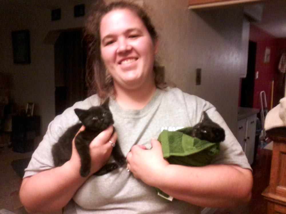 woman holding two black kittens