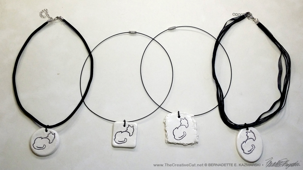 "All four pendants"". 1″ x 1″ round on flocked cord; 1″ x 1″ square on wire cord; 1.5″ x 1.5″ random on wire cord; 1″ x 1.5″ oval on multi-strand cord."
